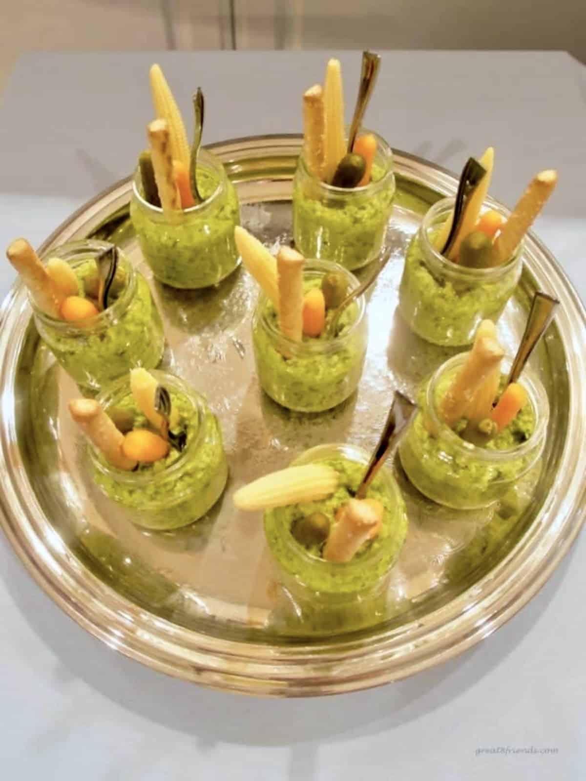 Vegetable dip being served in baby food jars with baby vegetables in each jar.