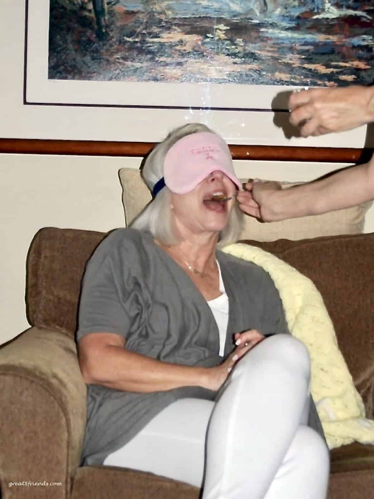 A woman with a pink blindfold on her eyes while someone is feeding her with a spoon.