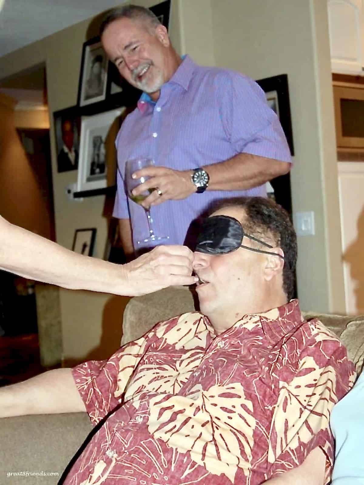 A man with a blindfold on his eyes while someone is feeding him and another man in the background watching with a smile.