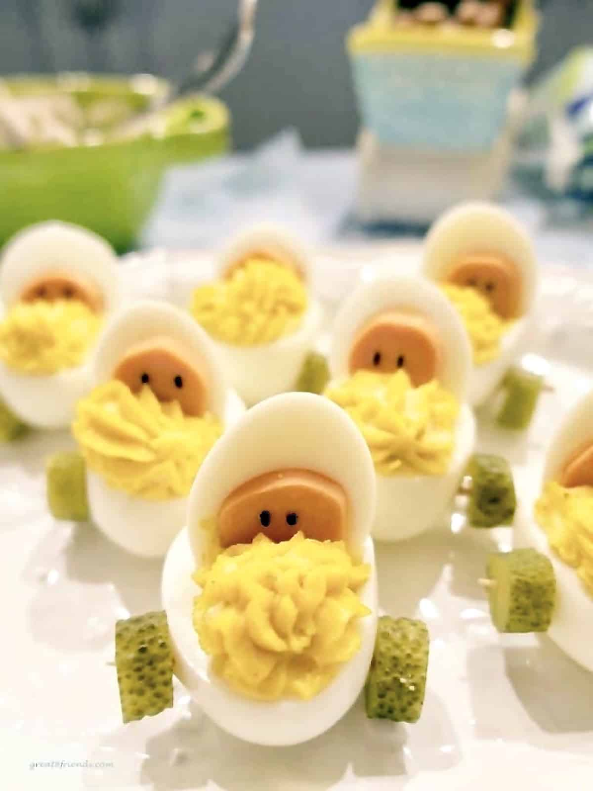 Deviled eggs prepared to look like babies in a baby carriage with sliced pickles as wheels.