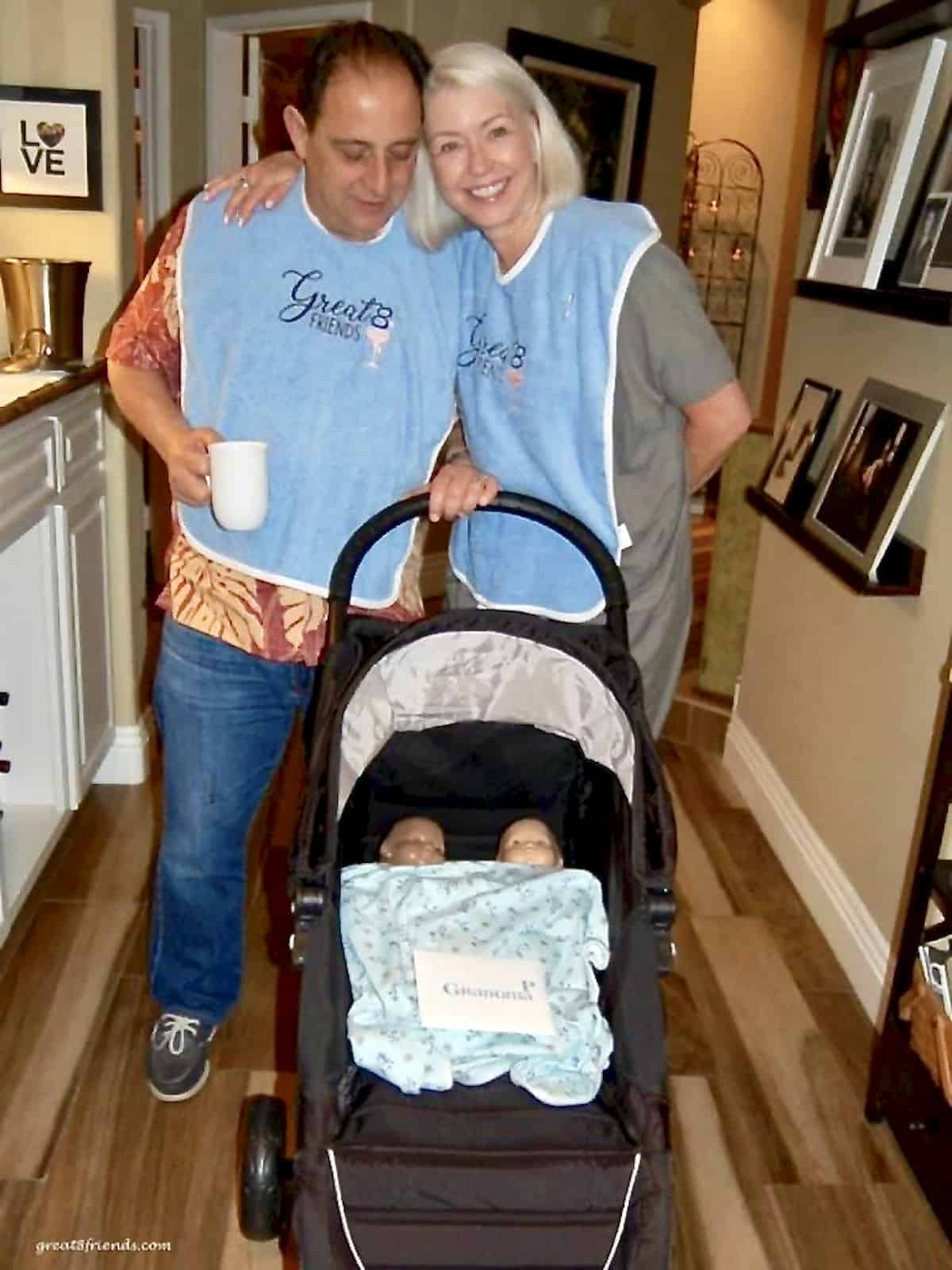 A man and a woman standing behind a black stroller with two baby dolls in it covered with a baby blanket.