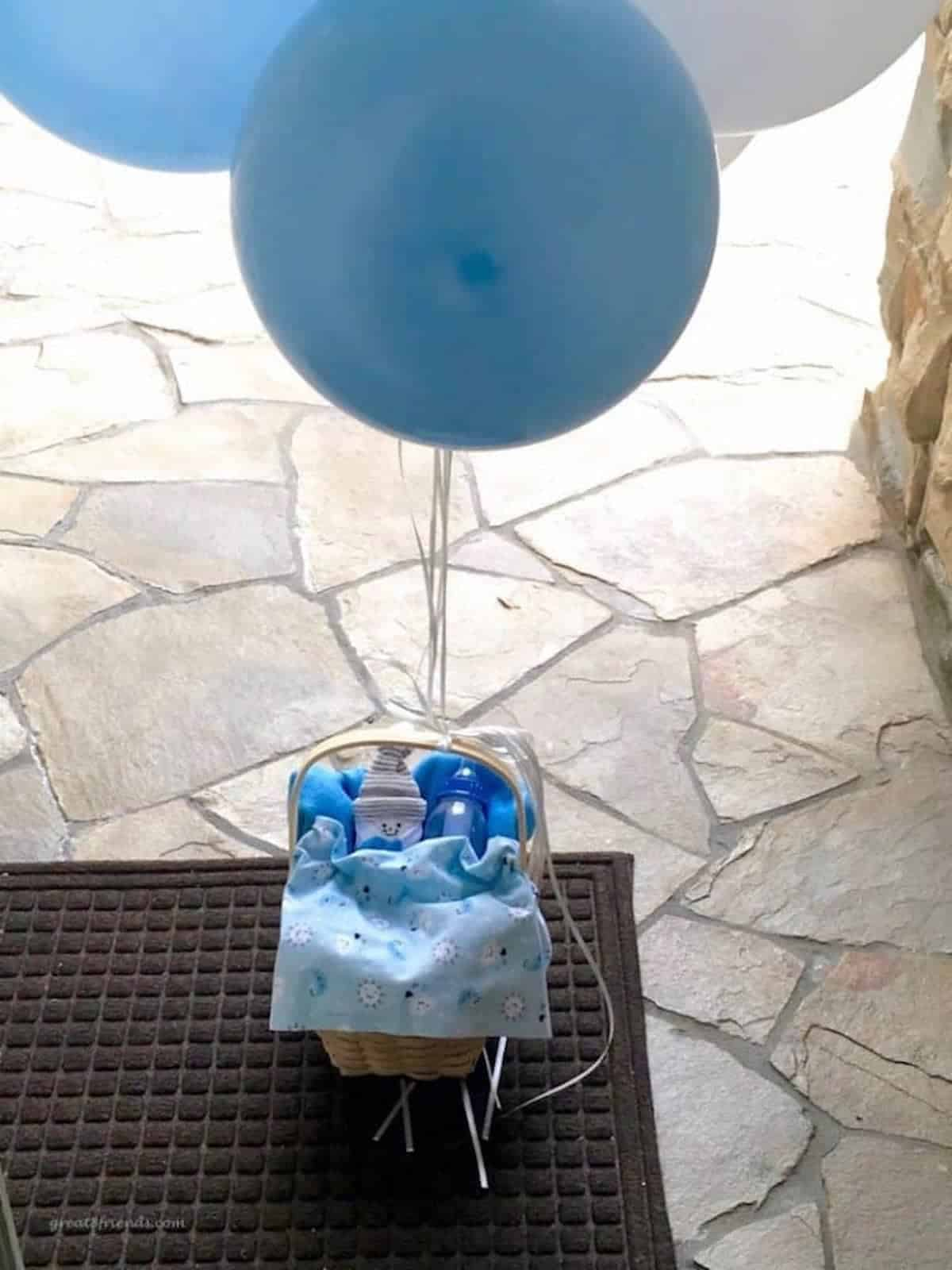 A basket with a baby bottle and a blue baby blanket on a porch with a blue balloon tied to the handle.