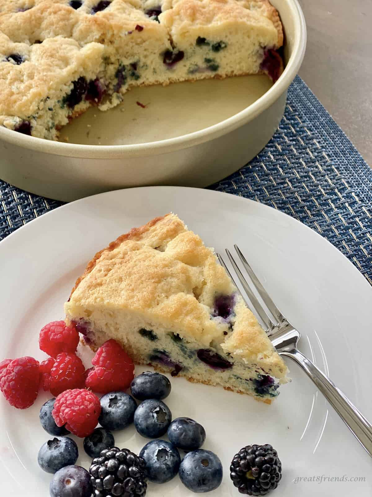 A piece of blueberry coffee cake on a plate with fresh blueberries and raspberries with a round cake pan with a piece of the coffee cake cut out of it.