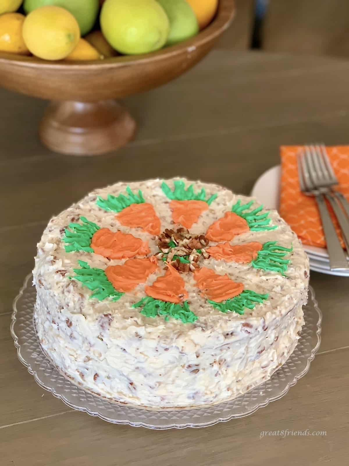 A carrot cake decorated with orange carrots topped with green icing carrot tops with a bowl of lemons in the background.