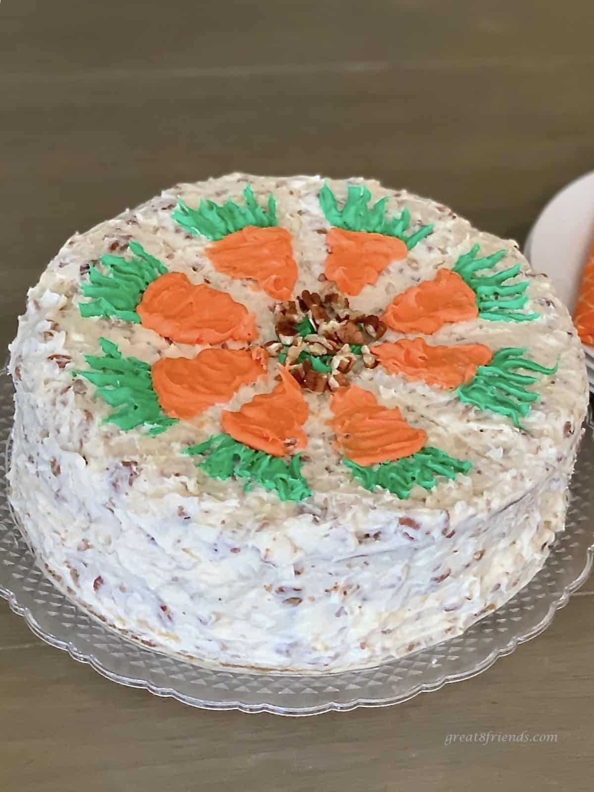 Two layer round carrot cake with pecan cream cheese frosting with pecans and decorated with icing carrots on the top.