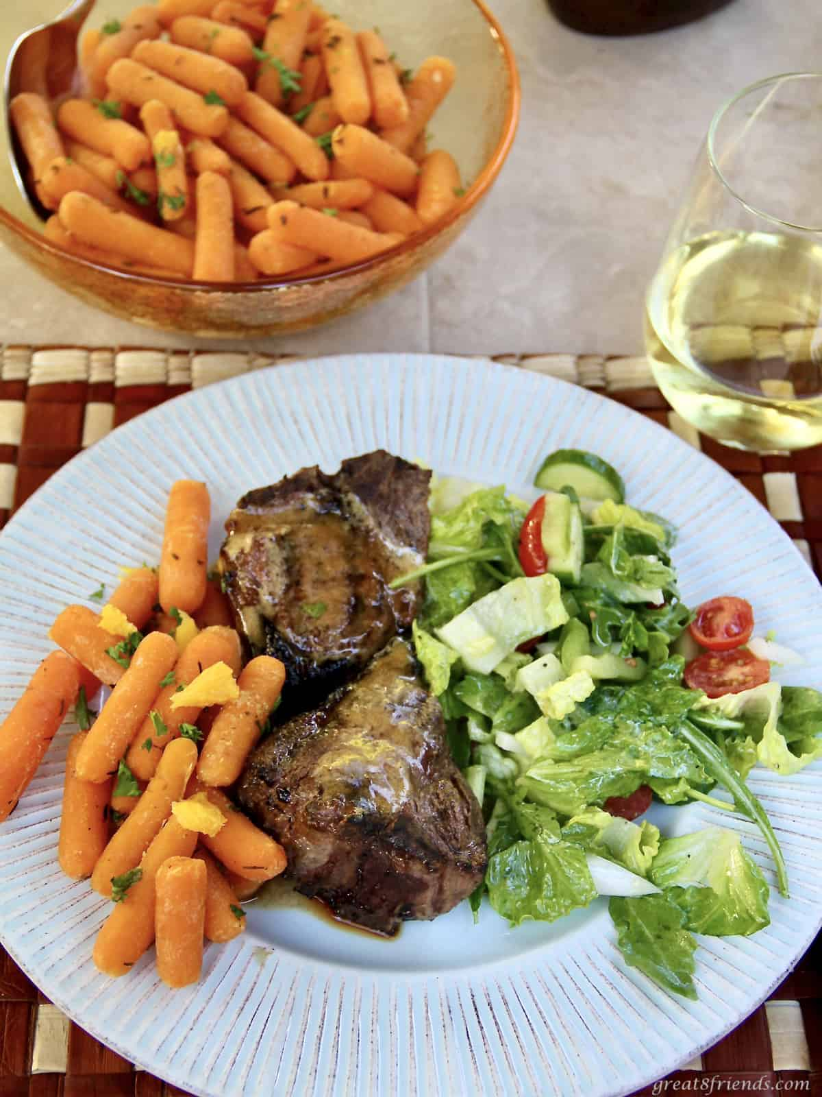A plate with carrots, lamb chops and a green salad with a bowl of carrots and a glass of wine on the side.