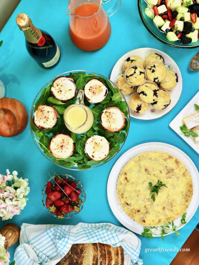 Overhead shot of an Easter brunch buffet table, eggs, muffins, quiche, strawberries.