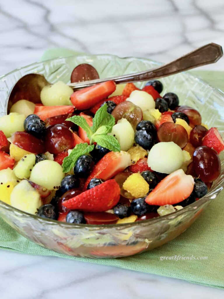 Fruit salad in a glass bowl on a green napkin.