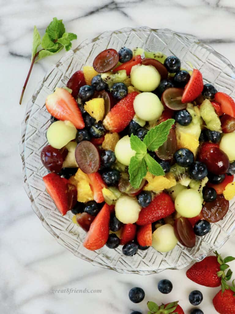 Overhead shot of fruit salad in a glass bowl on a marble slab.