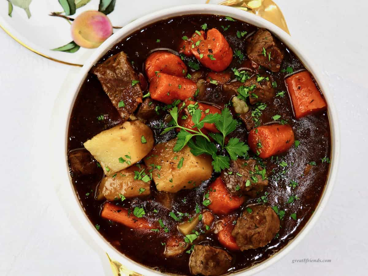 Overhead shot of beef stew in a ceramic serving dish.