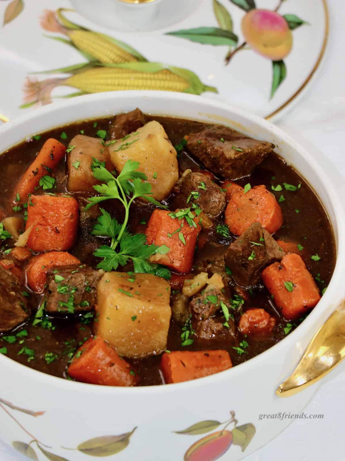 Beef stew in a ceramic casserole decorated with fruit.