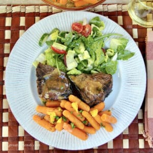 grilled lamb chops and orange glazed carrots on a plate with a small side green salad.