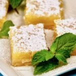 Close up of lemon bars topped with powdered sugar and garnished with a sprig of mint.