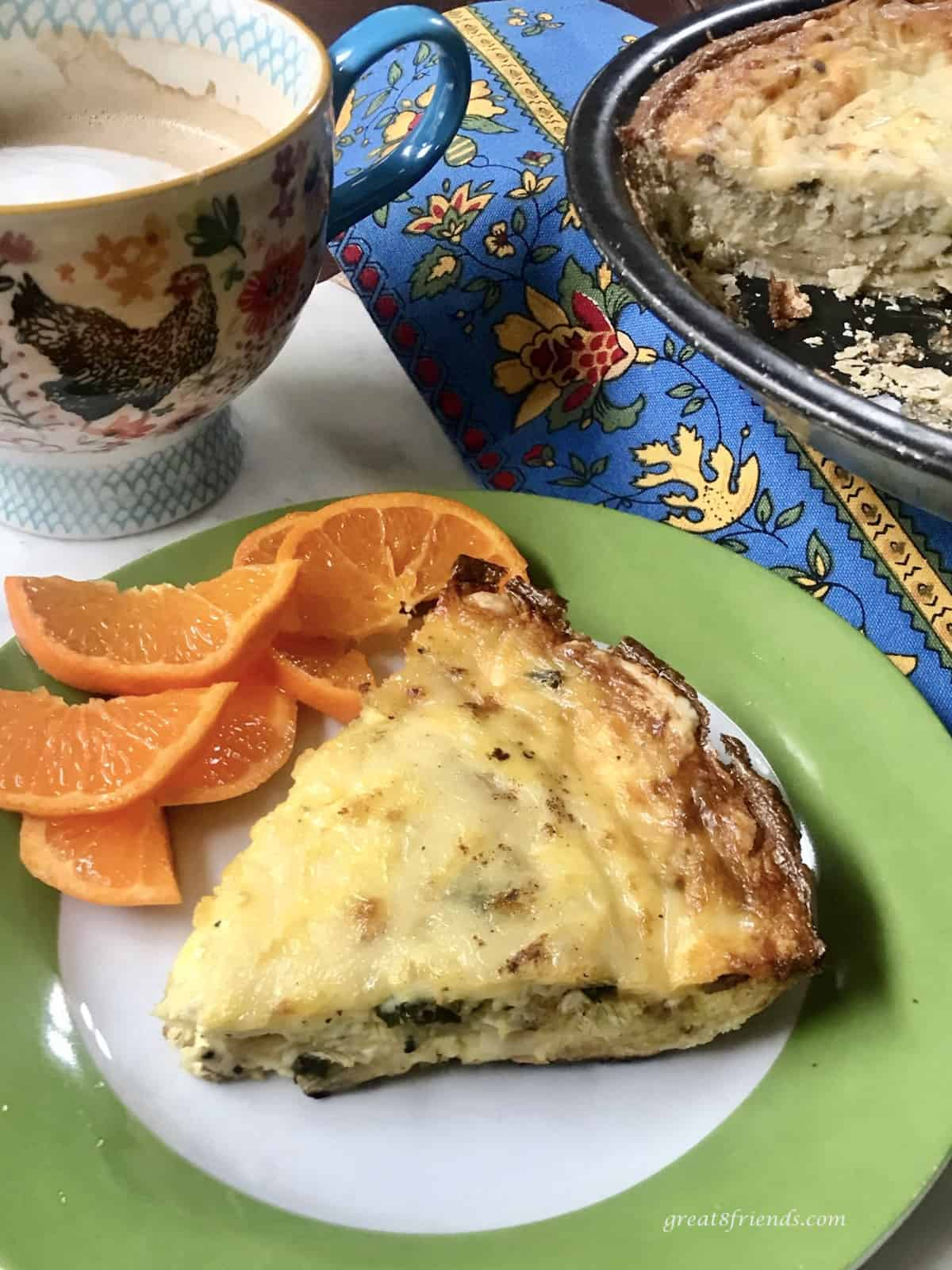 A slice of quiche lorraine on a white and green plate with orange slices and a cappuccino on the side.