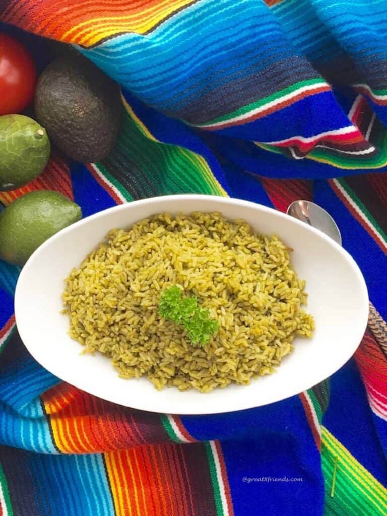 Baked rice with verde ingredients being served in a white oval bowl on a colorful Mexican serape with whole limes on the side.