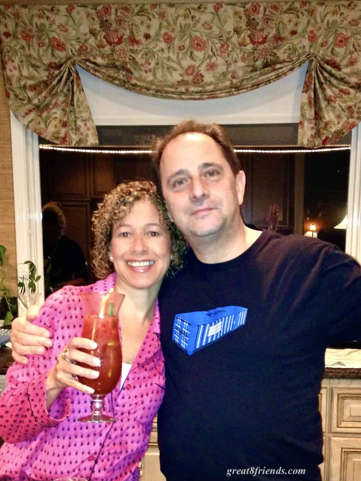 A man and woman posing for the camera and the woman has a tall glass with a Bloody Mary in it.