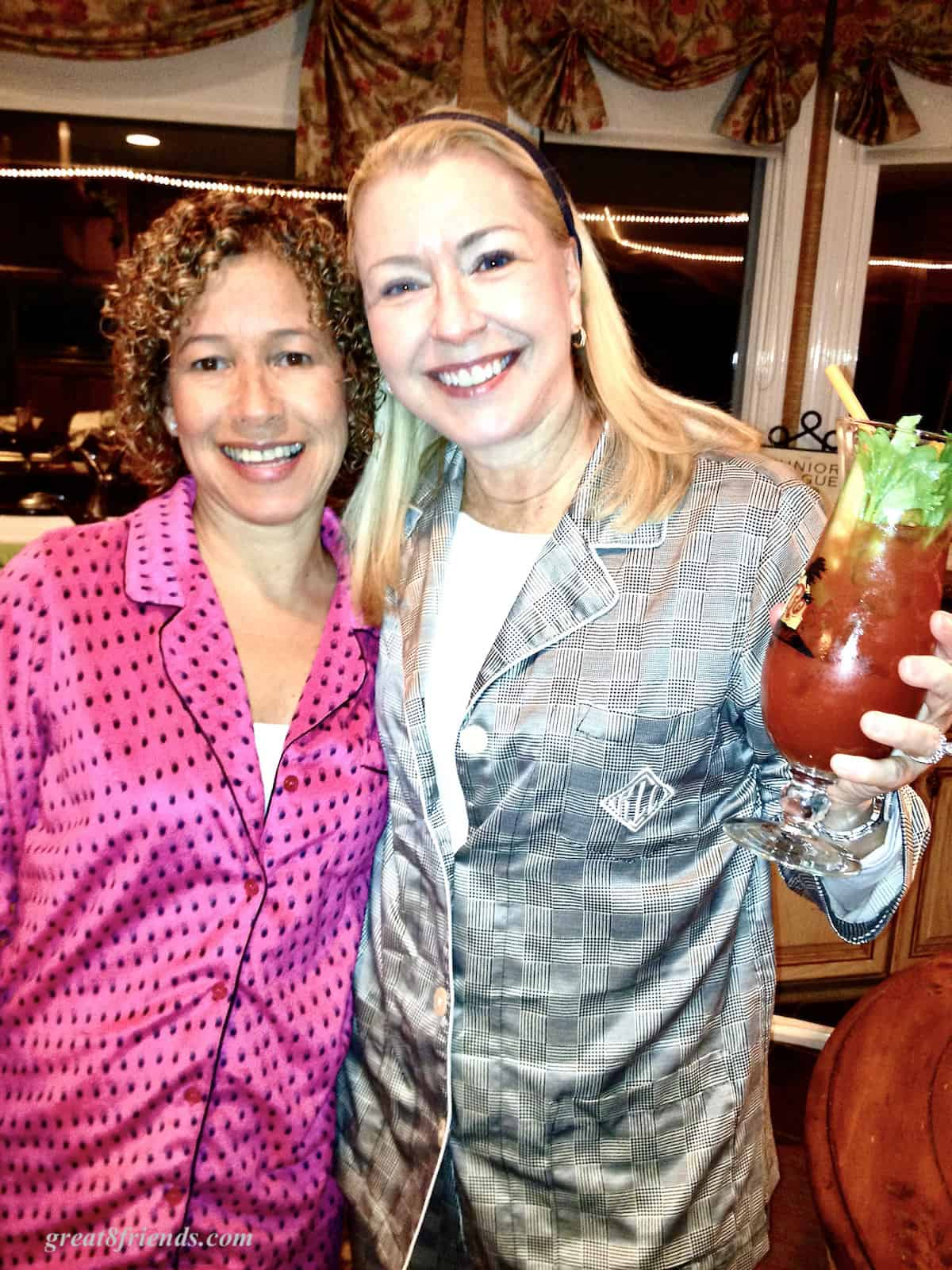 Two women posing for the camera one has a tall glass with a Bloody Mary in it.