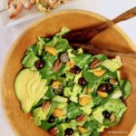 An overhead shot of salad with tangerine slices, pecans, grapes and avocados with wooden salad servers and a tray of grilled shrimp in the background.