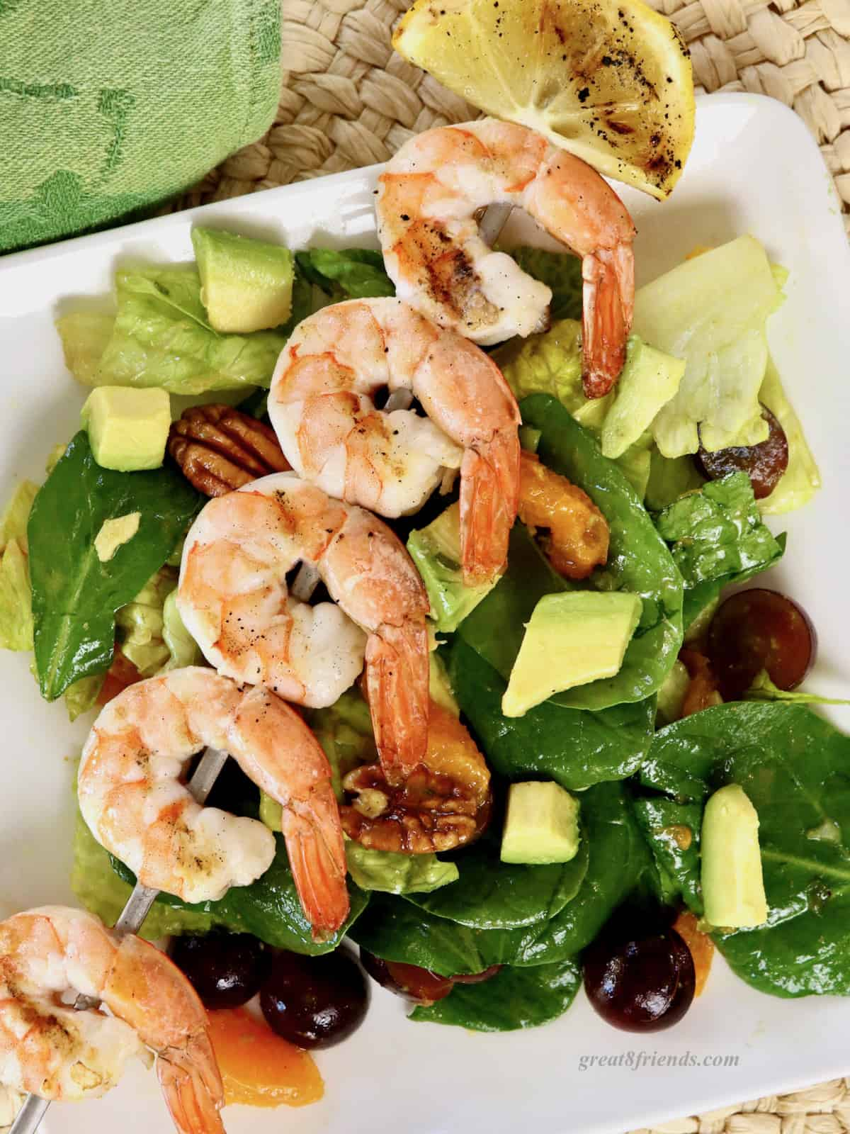 An overhead shot of a serving of salad with tangerine slices, pecans, grapes and avocados and a skewer of grilled shrimp on a square white plate, on a woven placemat.