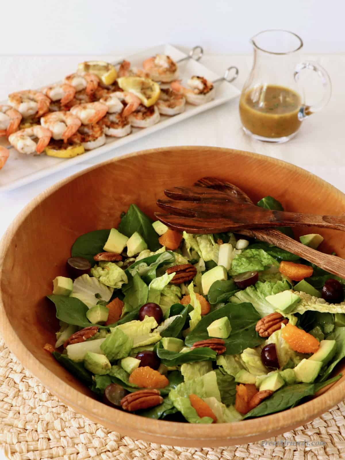 A salad with tangerine slices, pecans, grapes and avocados in a wooden bowl with a tray of grilled shrimp and pitcher of dressing in the background.