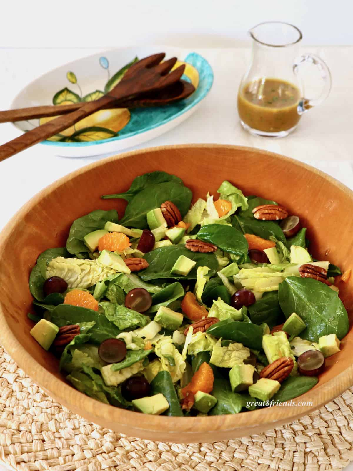 A curried spinach salad with tangerine slices, pecans, grapes and avocados in a wooden bowl with a pitcher of dressing and wooden salad servers in the background.