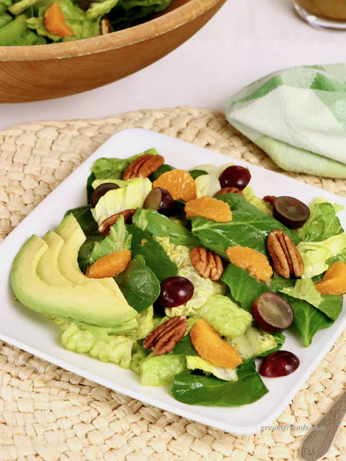 A serving of salad with tangerine slices, pecans, grapes and avocados on a square white plate, on a woven placemat with a green napkin and a wooden bowl of salad in the background.