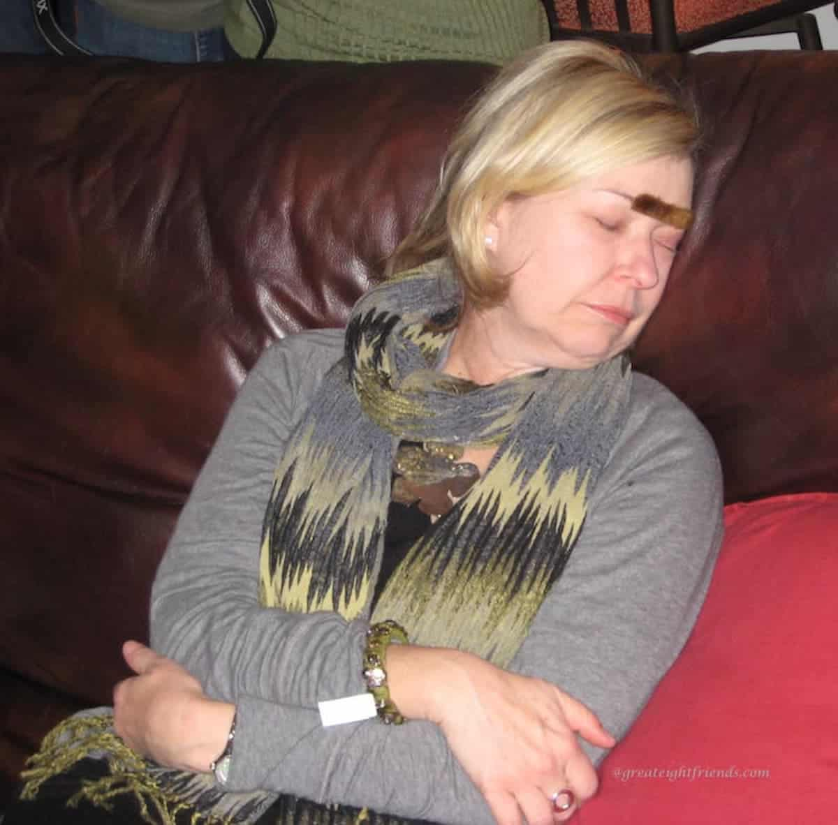 Woman asleep on a couch with a fake mustache on her forehead.