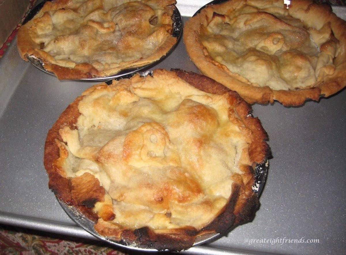 Three individual apple pies on a baking sheet.