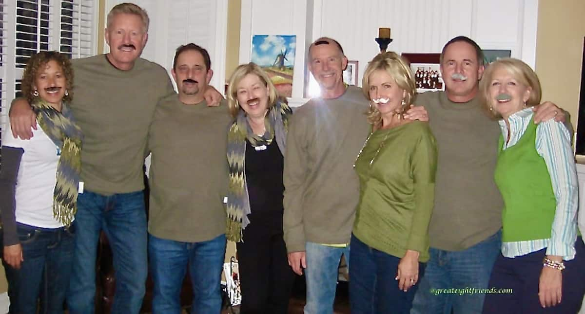 Group of eight people posing for the camera with fake mustaches on.