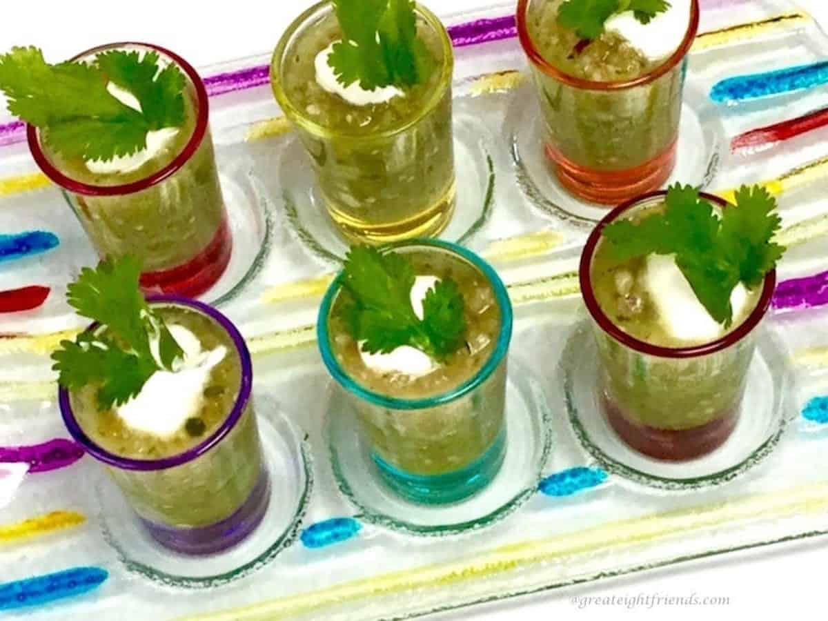 Green gazpacho cold soup being served in six colored glass small shot glasses.