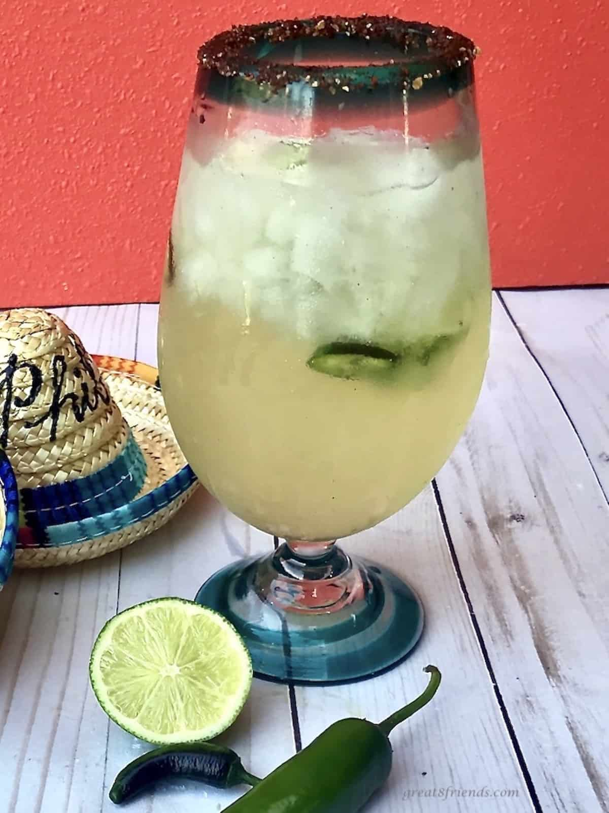 Large glass filledwith ice and a margarita with limes and jalapeños on the table and two mini sombreros with names written on them.