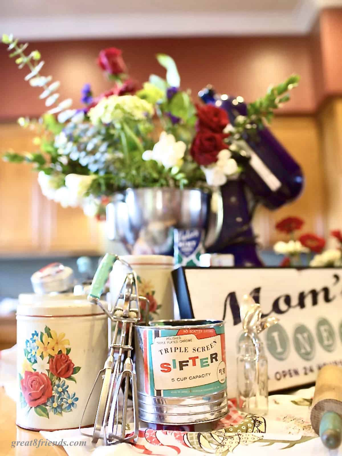 An island kitchen with several kitchen decorations like a bouquet of flowers in a mixing bowl, a sifter, a sign that says Mom's kitchen, and a rolling pin.