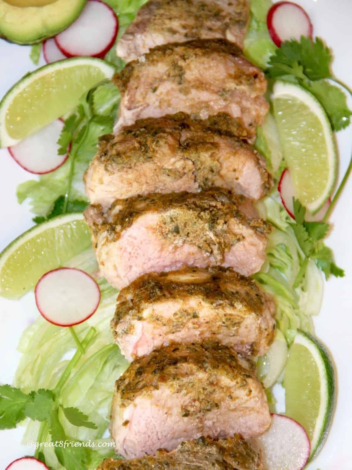 Sliced pork tenderloin on a platter with an adobe sauce on top laying on lettuce, cilantro, limes and sliced radishes.