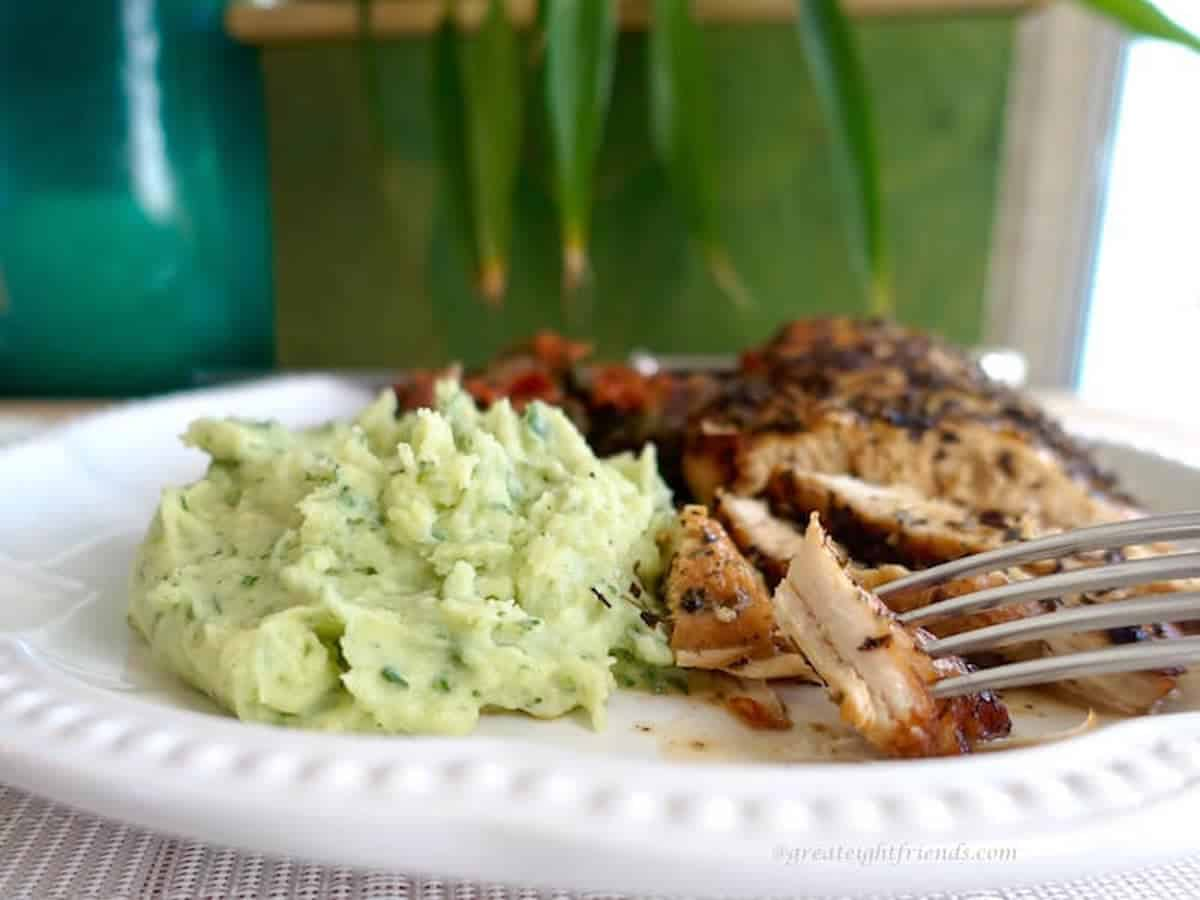 A white dinner plate with basil pureed potatoes and roasted chicken on it.
