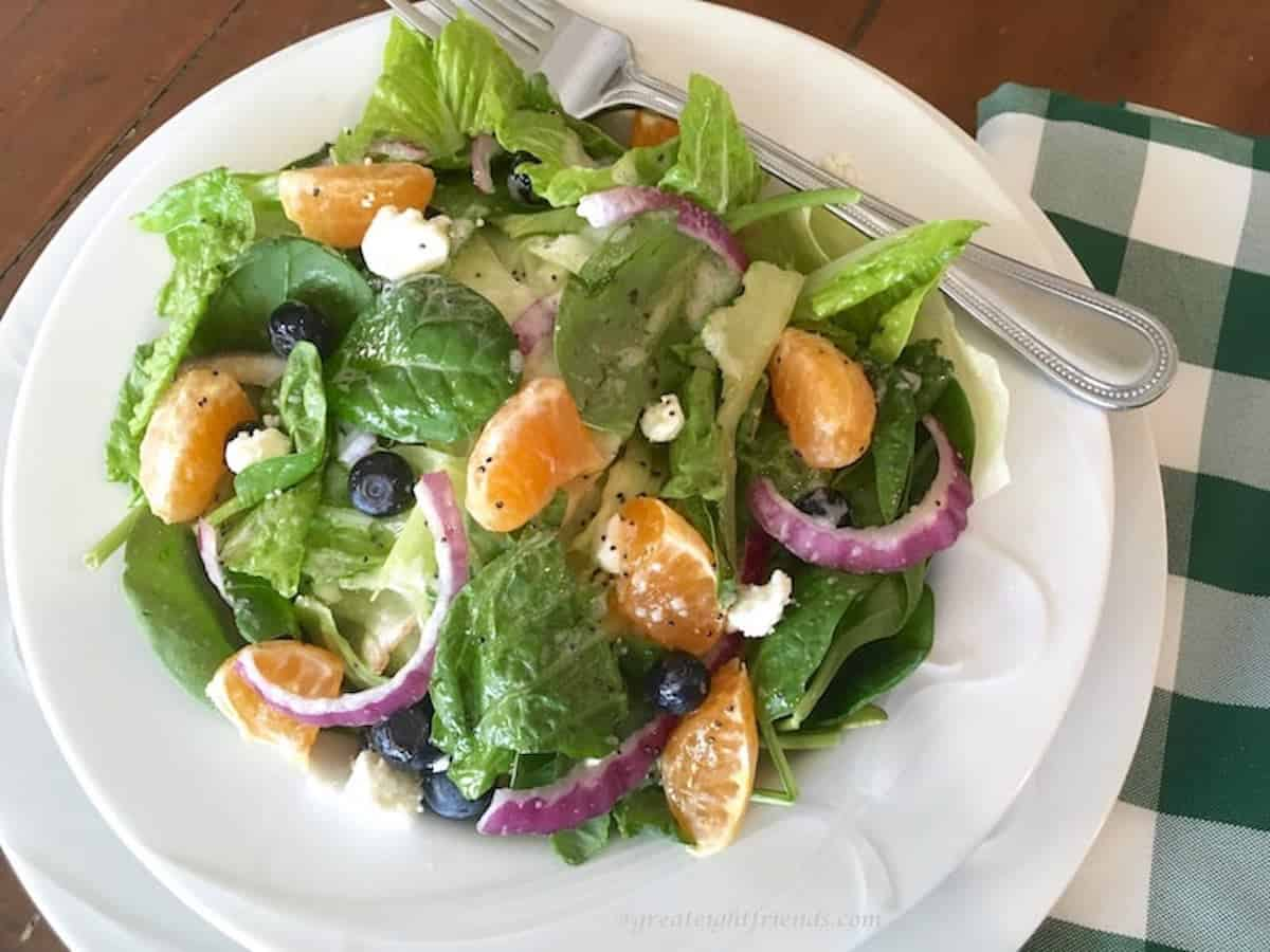 Spinach, orange, red onion salad served with a poppyseed dressing on a white plate.
