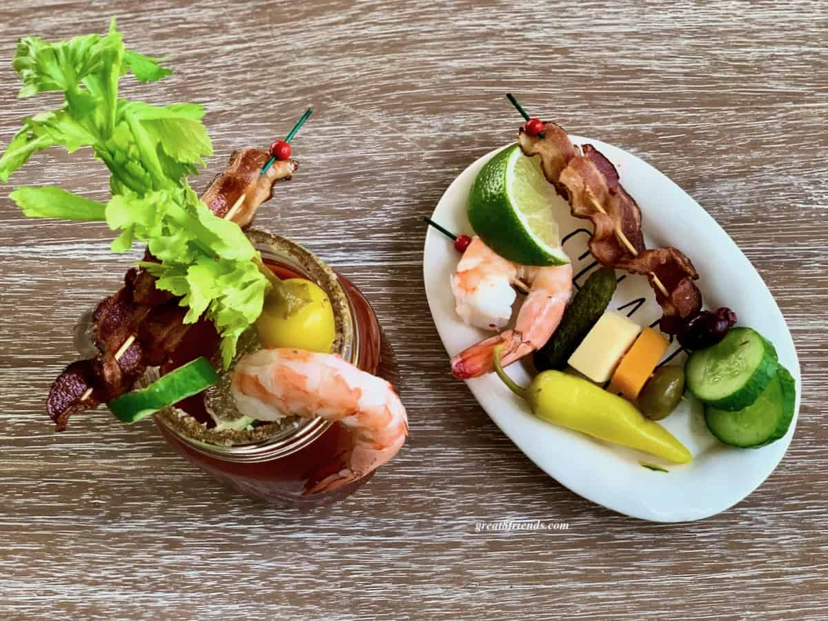 Overhead shot of a white oval plate with a shrimp, slice of lime, skewer of bacon, some cucumbers slices a pickled pepper and some cheese squares alongside a fully loaded bloody mary.