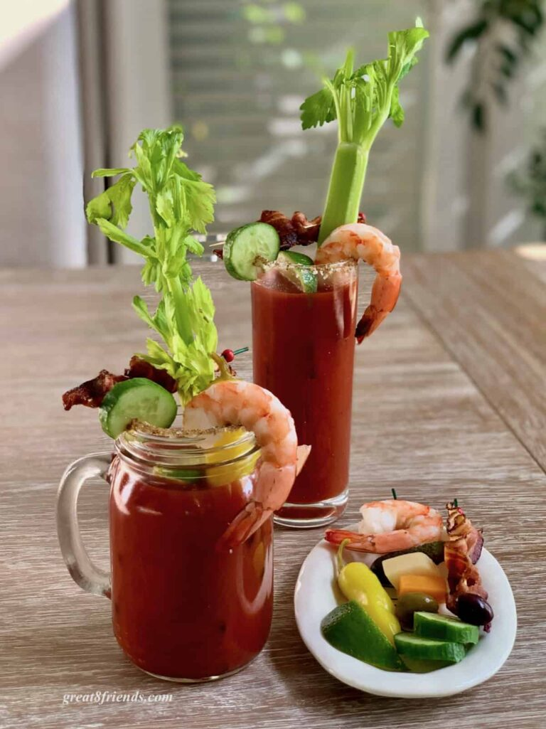 A bloody mary in a glass mug with a shrimp hanging off the side, a slice of cucumber hanging on the side. There's another bloody Mary in the background along with a small plate of extra garnishes.