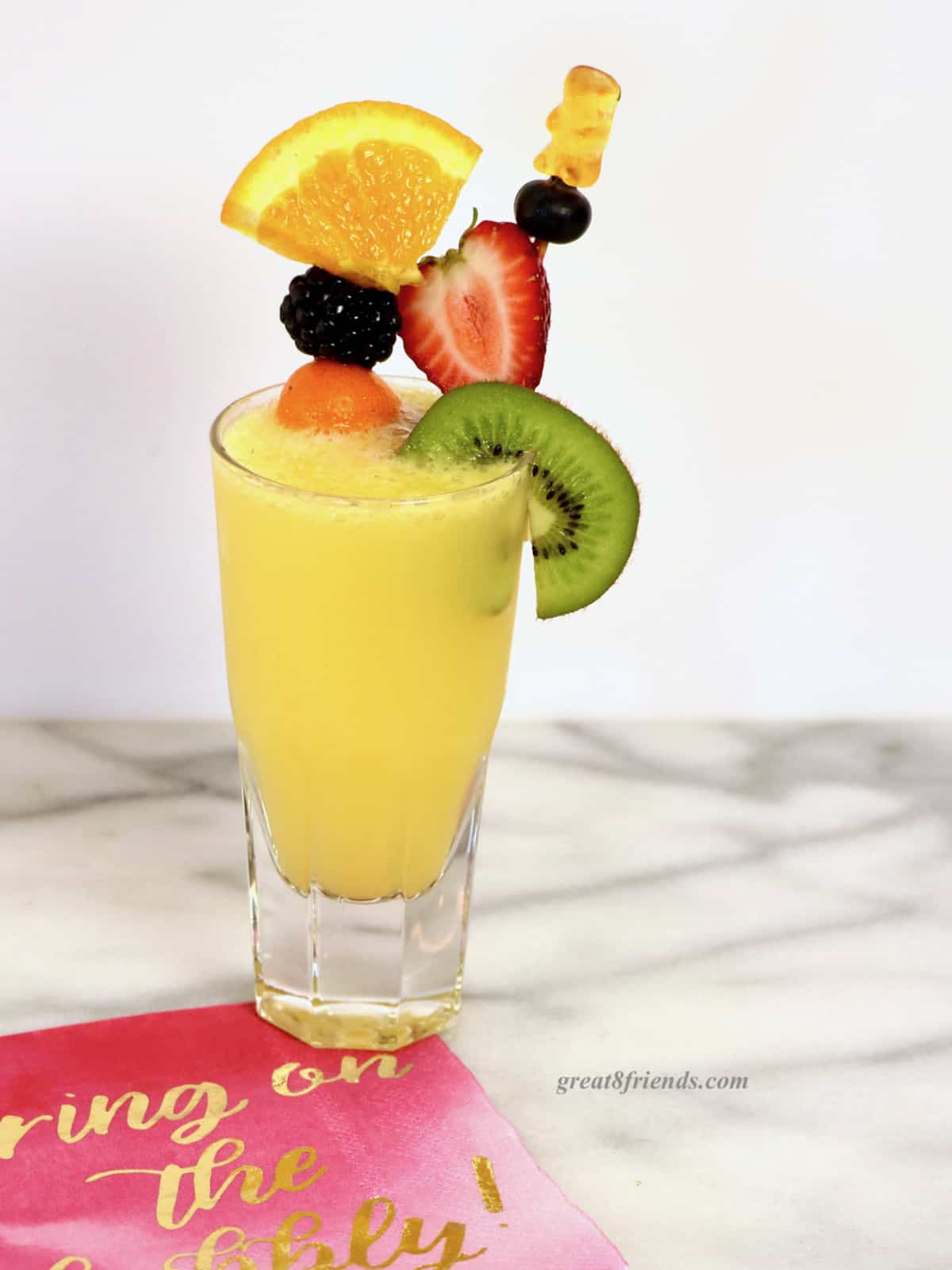 A mimosa in a juice glass garnished with two skewers of assorted fruit on a pink napkin.