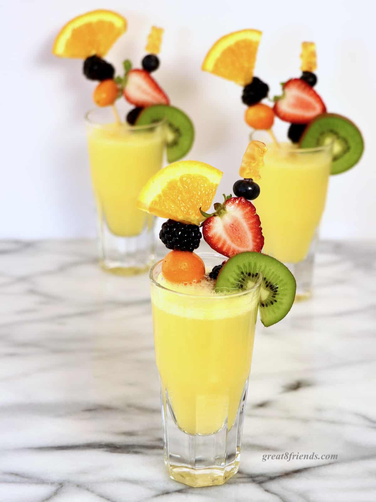 A mimosa garnished with 2 skewers of fresh fruit, with 2 more mimosas in the background.