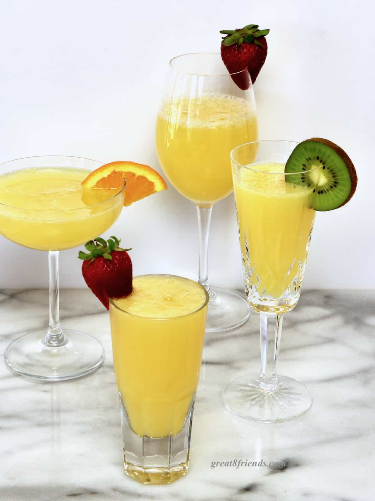 Four mimosas each in a different glass; one wine glass garnished with a strawberry, one coupe glass garnished with an orange slice, one flute garnished with a slice of kiwi, one juice glass garnished with a strawberry.