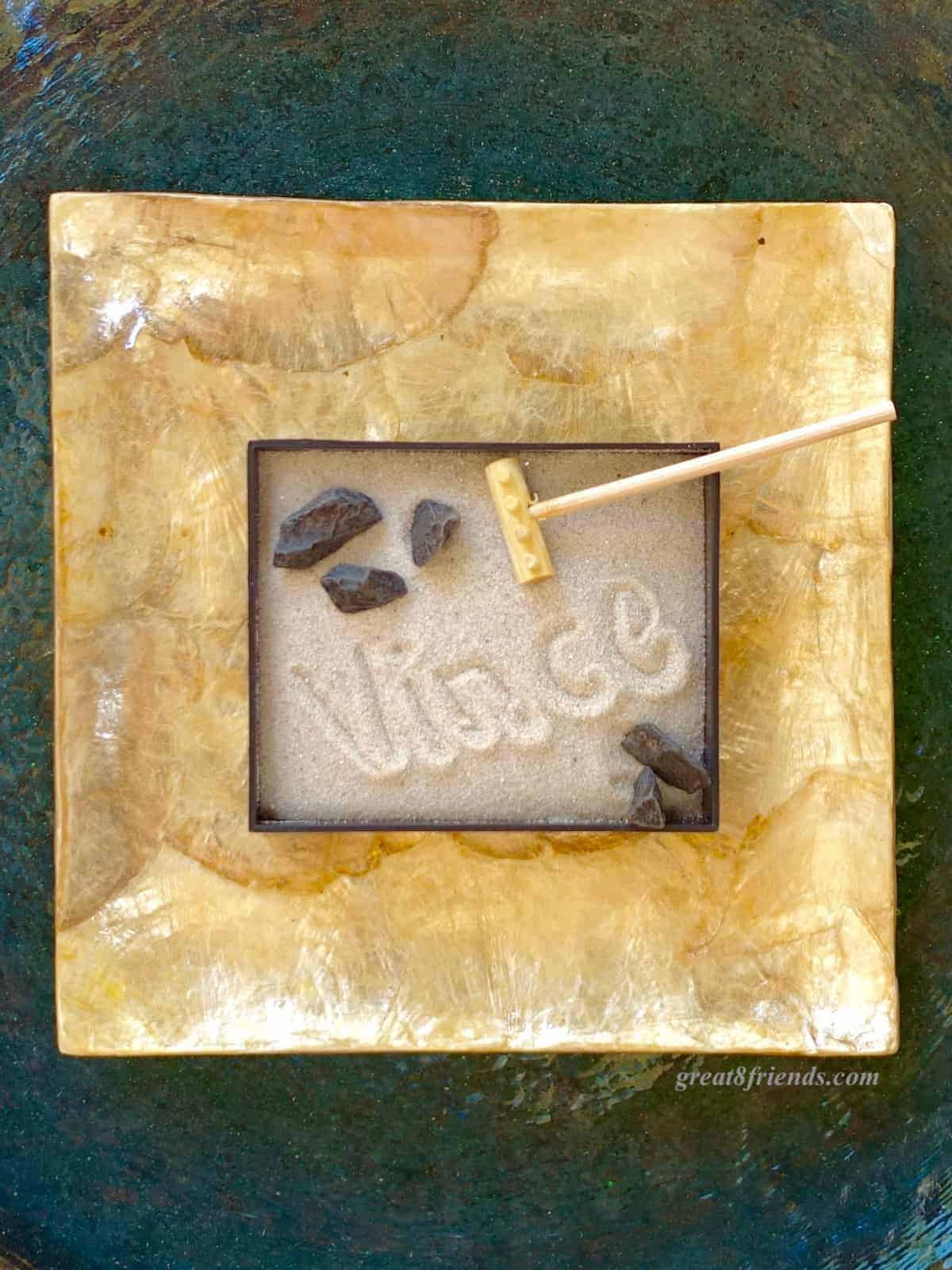 Overhead shot of a mini Zen garden with 4 small rocks, a small rake and the name Vince written in the sand.