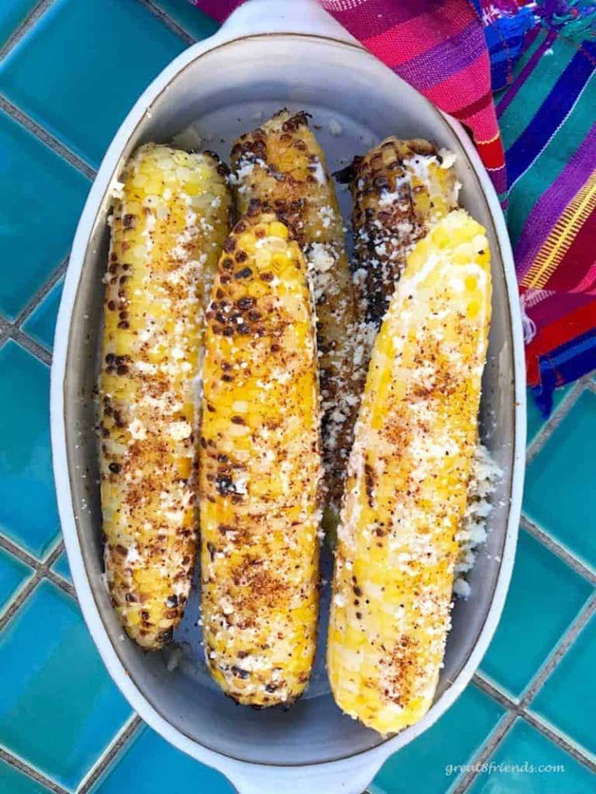 Grilled corn on the cob in an oval white baking dish with a colorful napkin on the side.