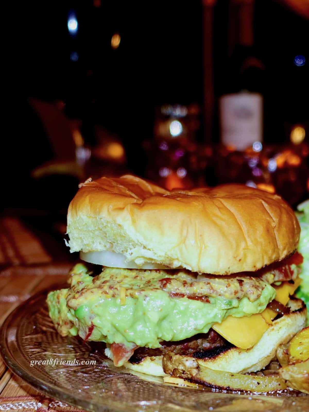 Grilled hamburger on a bun with cheese, mustard and guacamole.