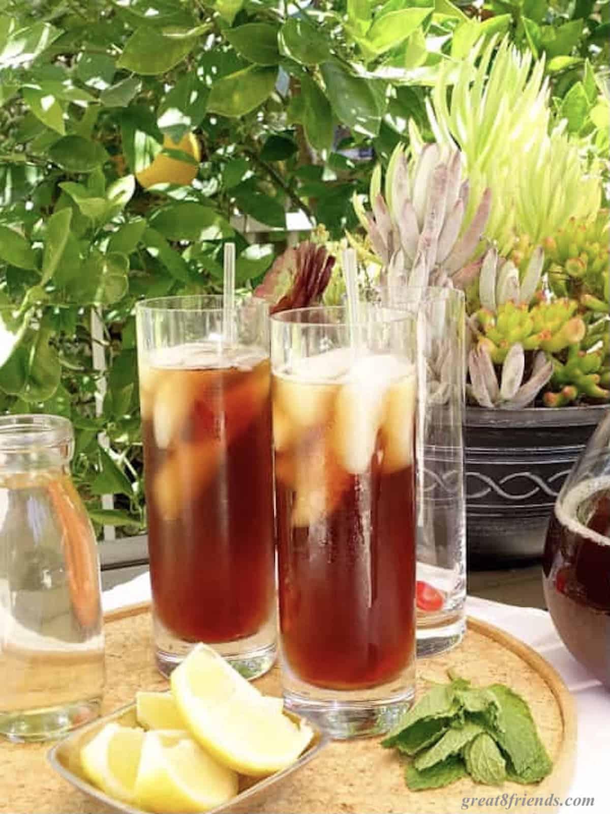 Two glasses of iced tea on a tray with some lemon wedges and mint leaves.